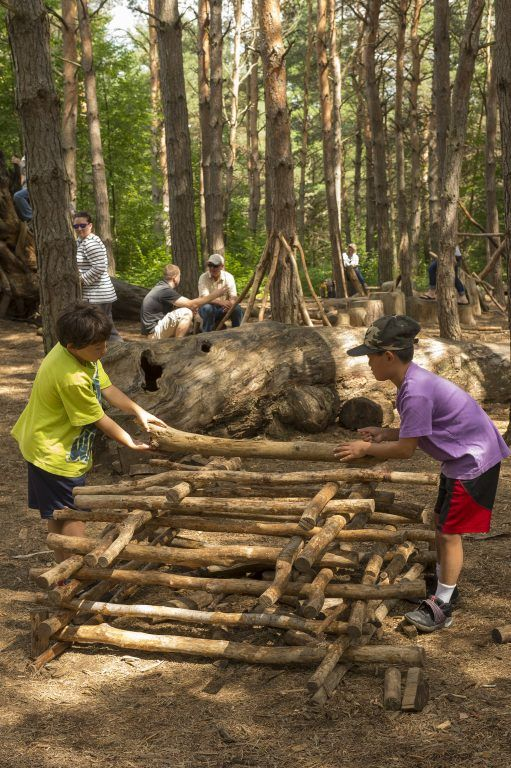 kids build a stick fort in the Pines Play area
