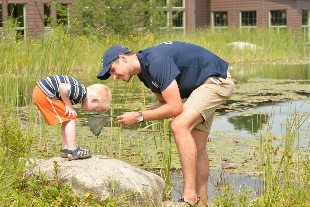 Naturalist helps young guest explore life in Greenleaf Pond.